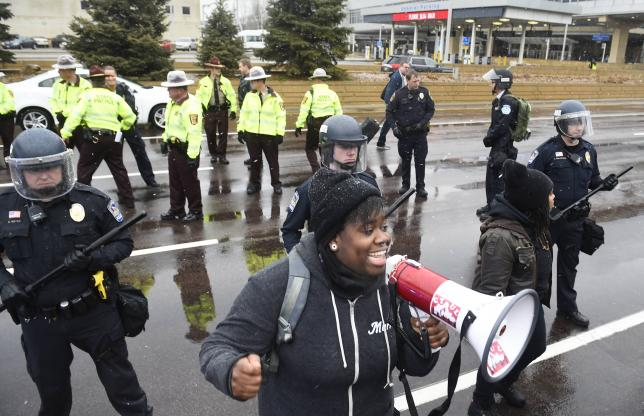 A protester named Oluchi of Minneapolis speaks to protesters after they shut down the main road to the Minneapolis St. Paul Airport following a short protest at the Mall of America in Bloomington, Minnesota December 23, 2015. Credit: REUTERS/Craig Lassig