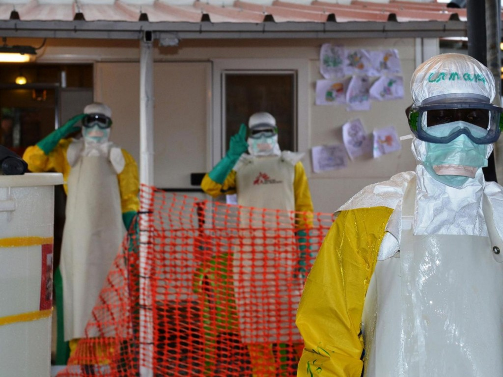 Health workers wearing protective gear gesture at the Nongo ebola treatment centre in Conakry, Guinea. Credit: The Independent UK/CELLOU BINANI/AFP/Getty Images