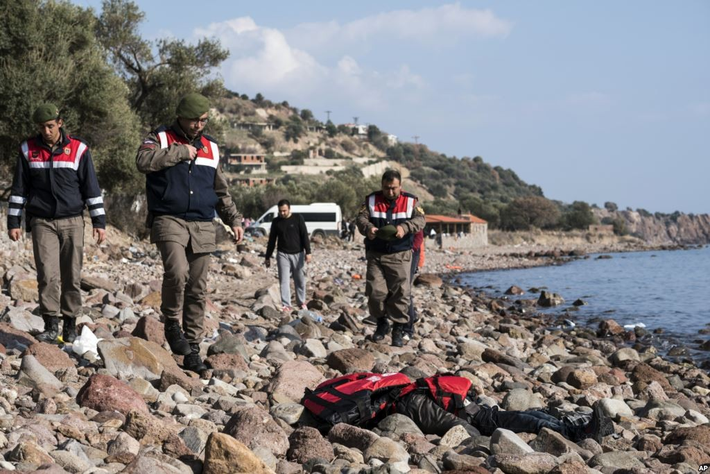 Turkish paramilitary police officers stand near a dead body of a migrant on the beach near the Aegean town of Ayvacik, Canakkale, Turkey, Jan. 30, 2016. Credit: Voice of America
