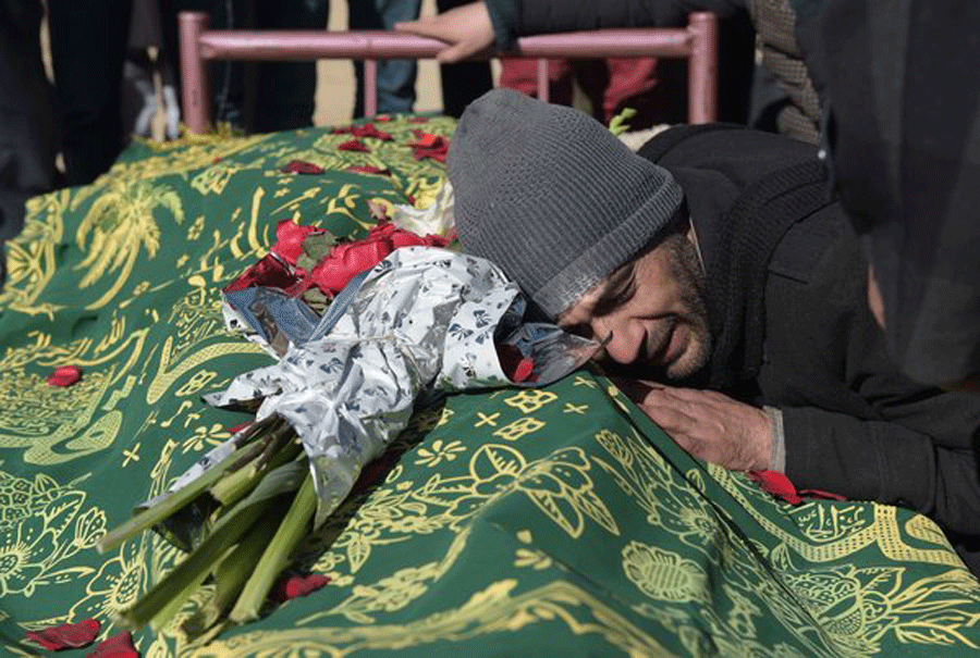 A relative grieved at the body of a man who was killed in a suicide attack on employees of Tolo Television in Kabul on Jan. 21. Credit Shah Marai/Agence France-Presse — Getty Images / The New York Times