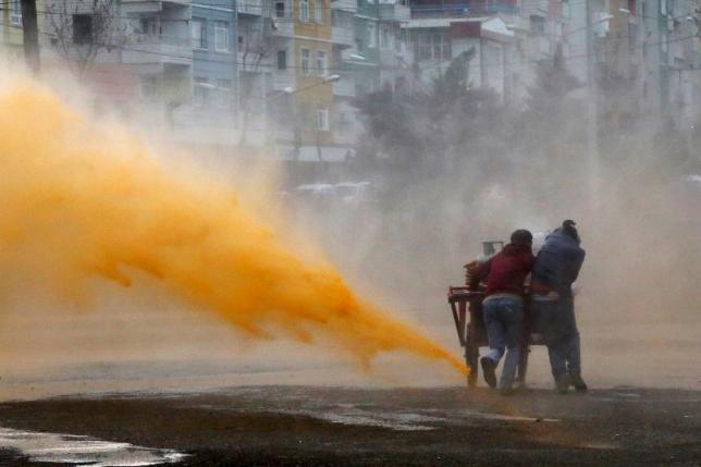 Street vendors take cover as Turkish riot police use a water cannon to disperse Kurdish demonstrators during a protest against the curfew in Sur district, in the southeastern city of Diyarbakir, Turkey February 21, 2016. Credit: REUTERS/Sertac Kayar