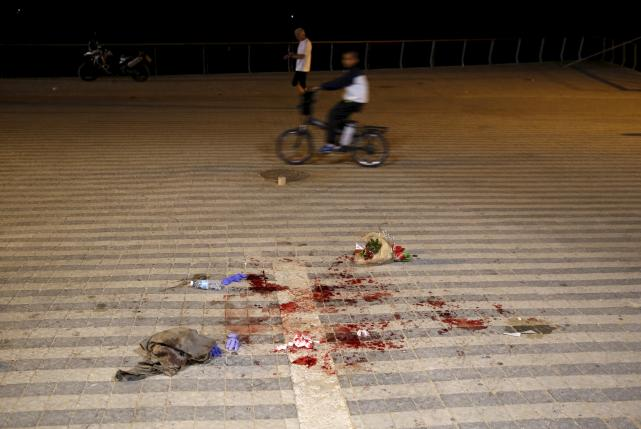 A boy rides past blood stains where, according to Israeli police spokesperson, at least 10 Israelis were stabbed, in the popular Jaffa port area of Tel Aviv, Israel March 8, 2016. Credit: REUTERS/Amir Cohen