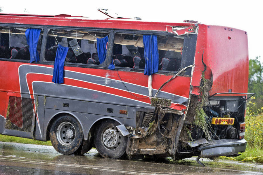 A damaged OGA Charters bus is hauled away after a fatal rollover Saturday left eight people dead and over 40 others injured. Image Credit: First Coat News
