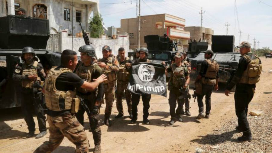 Iraqi troops hold Islamic State flag upside down