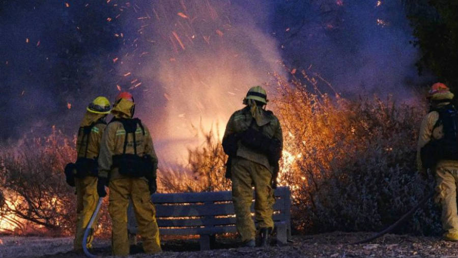 Firefighters watching as fire continues to burn in the foothills outside of Calabasas, Calif.