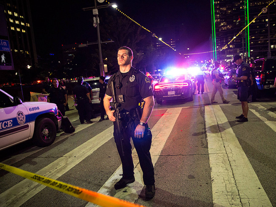 A Dallas Police officer stays vigilant following the shooting that took the lives of five police officers, wounded seven other policemen and injured two civilians.