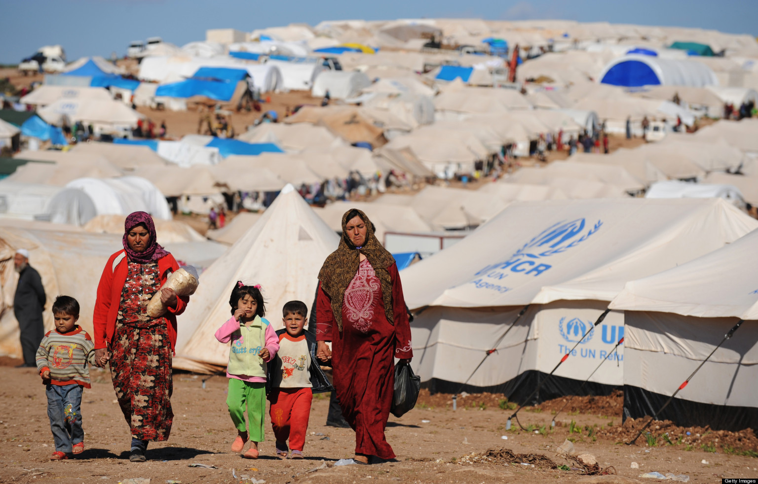 Syrian internally displaced people walk in the Atme camp, along the Turkish border in the northwestern Syrian province of Idlib, on March 19, 2013. Credit: The Huffington Post/AFP PHOTO/BULENT KILIC (Photo credit should read BULENT KILIC/AFP/Getty Images)