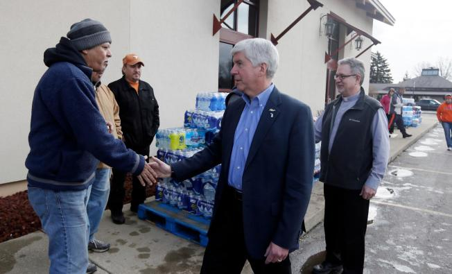 Michigan Gov. Rick Snyder, center and Our Lady of Guadalupe Church Deacon Omar Odette, right, meet with volunteers helping to load vehicles with bottled water in Flint, Mich. Credit: US News/Carlos Osorio/AP