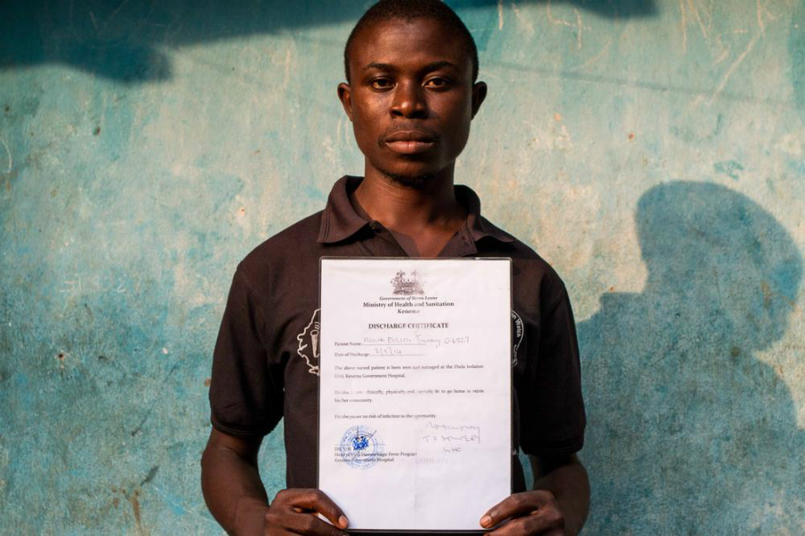 An Ebola survivor, named Ericson Musa, from Sierra Leone, holding his Discharge Certificate. Photo: Al Jazeera