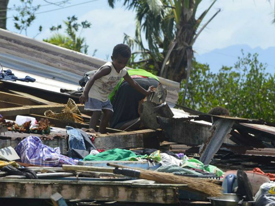 A child crawls in the wreckage of a home destroyed by Tropical Cyclone Winston in Fiji. Credit: ABC