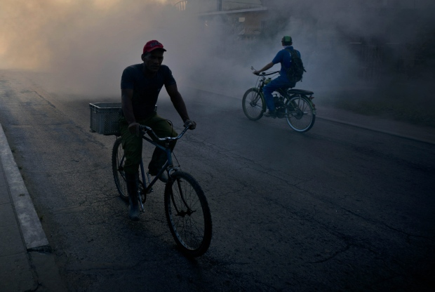 People make their way through fumigation fog, sprayed to kill Aedes aegypti mosquitoes that spread Zika, chikungunya and dengue, in Pinar del Rio, Cuba. Credit: CBC News/Ramon Espinosa/Associated Press