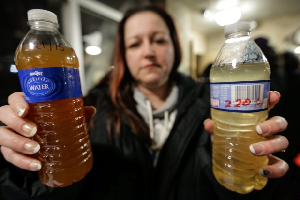 A resident from Flint shows a bottle filed with contaminated tap water. Photo: Kyle Luellen/BSO