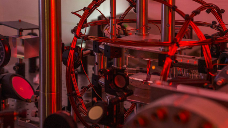 The experiment, featuring the small red glow of a BEC trapped in infrared laser beams. Credit: Stuart Hay, ANU / Science Daily