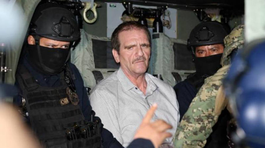 The photo released on Thursday shows Palma being taken into custody alongside a couple officials involved in his capture. Image Credit: Deccan Chronicle