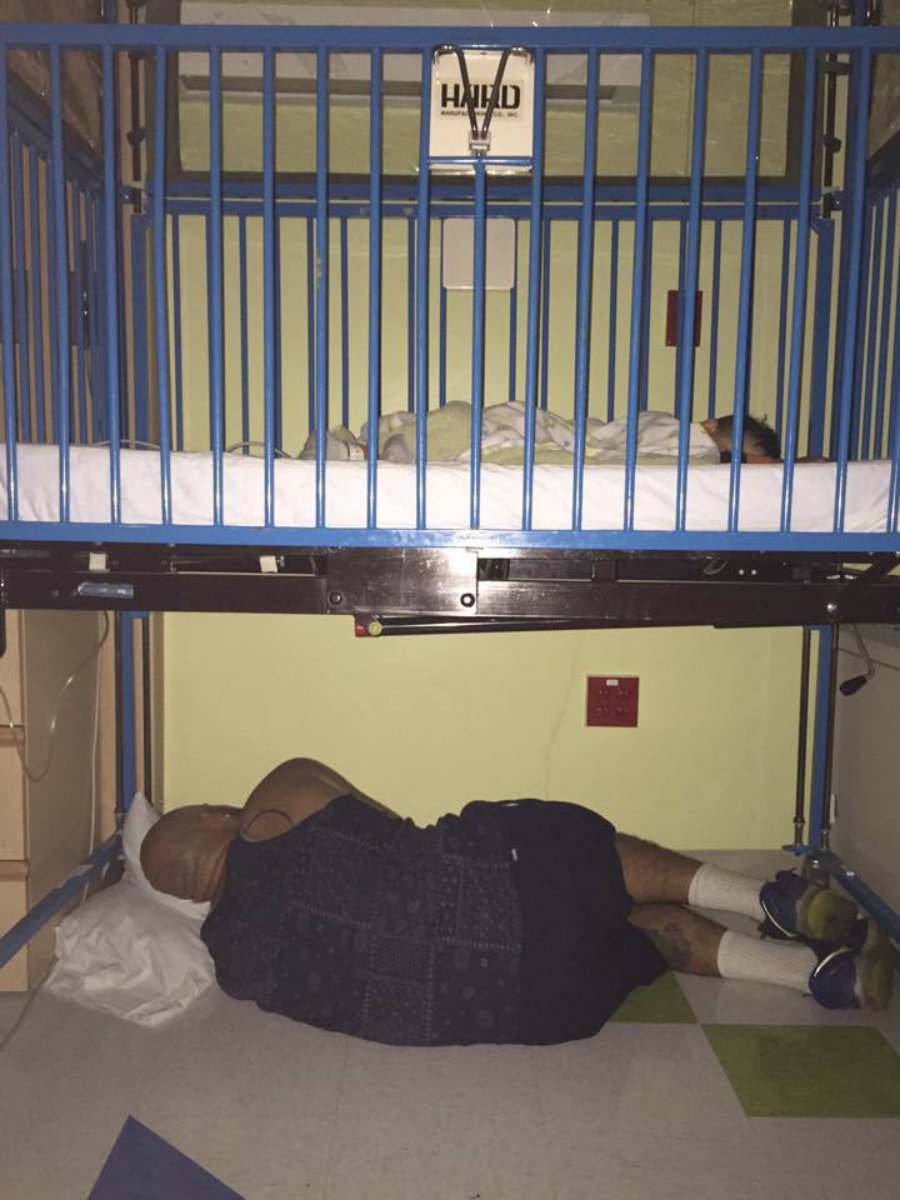 A picture of a father sleeping under the bed where his sick son was sleeping has gone viral. His wife, Amy Palmer, took the picture that shows the man lying on the floor underneath Andre Jesse, her son. Photo credit: Amy Palmer / KTLA5