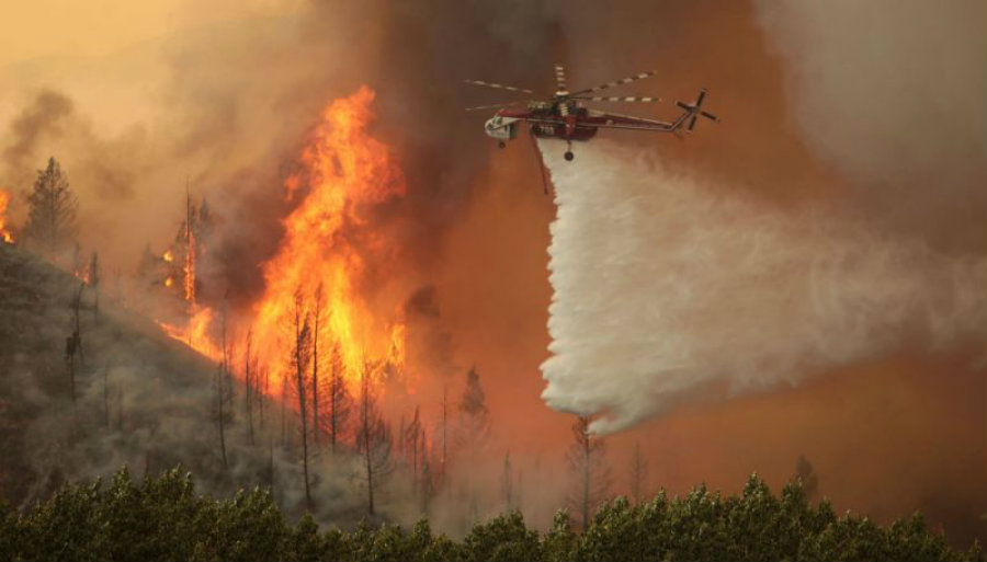 A rescue helicopter drops water over the fire in Idaho trying to bring down the intense flames. Image Credit: Yahoo